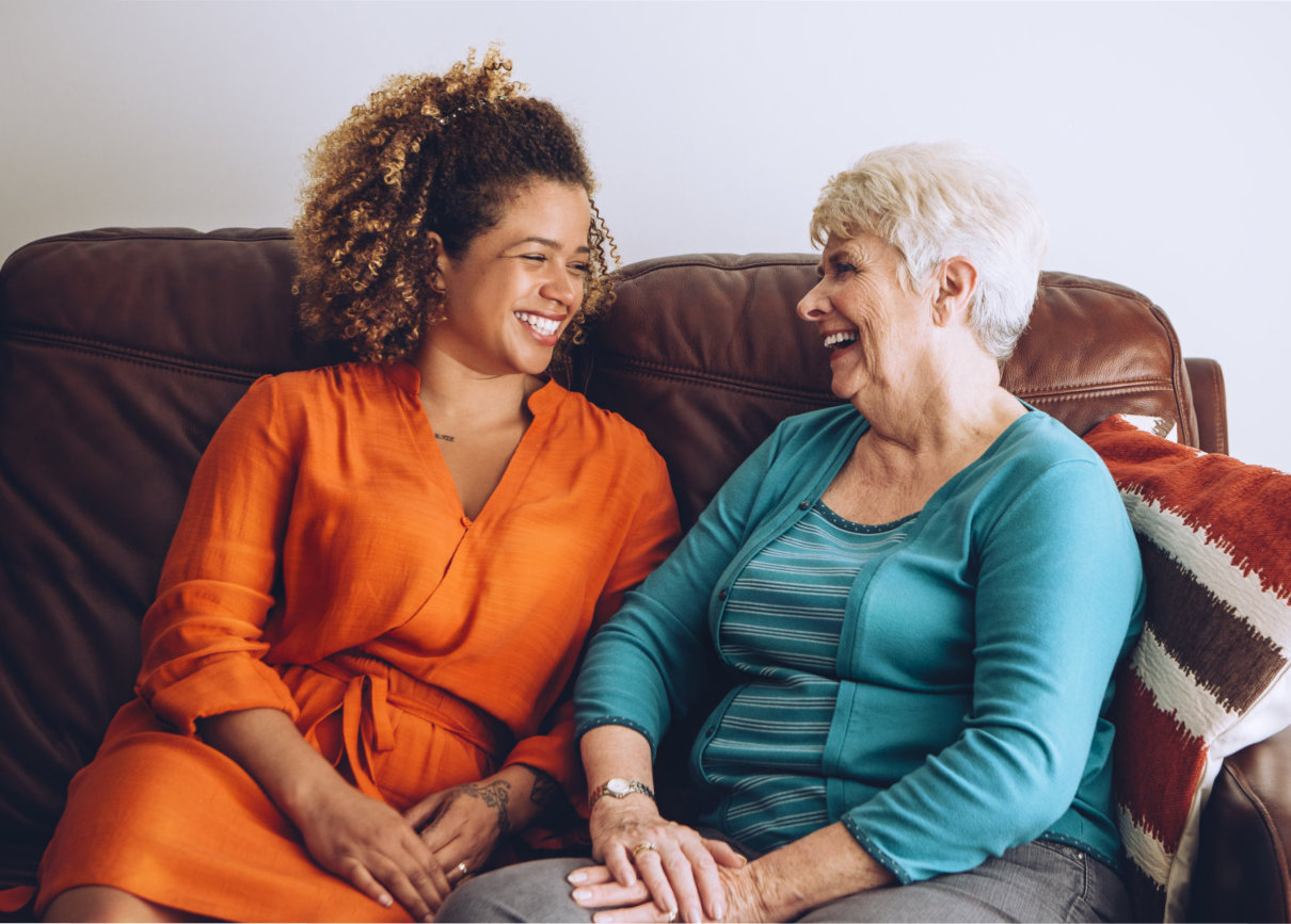 a caregiver and a senior woman laughing together