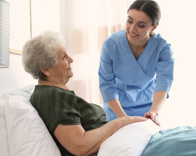 a caregiver checking the condition of a senior woman in bed